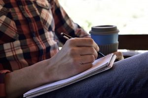 Man writing on a notebook with a cup of coffee
